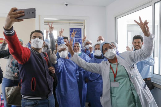 Moroccan patients who recovered from the novel coronavirus disease celebrate with the medical staff as they leave the hospital in the city of Sale, north of the capital Rabat, on April 3, 2020.