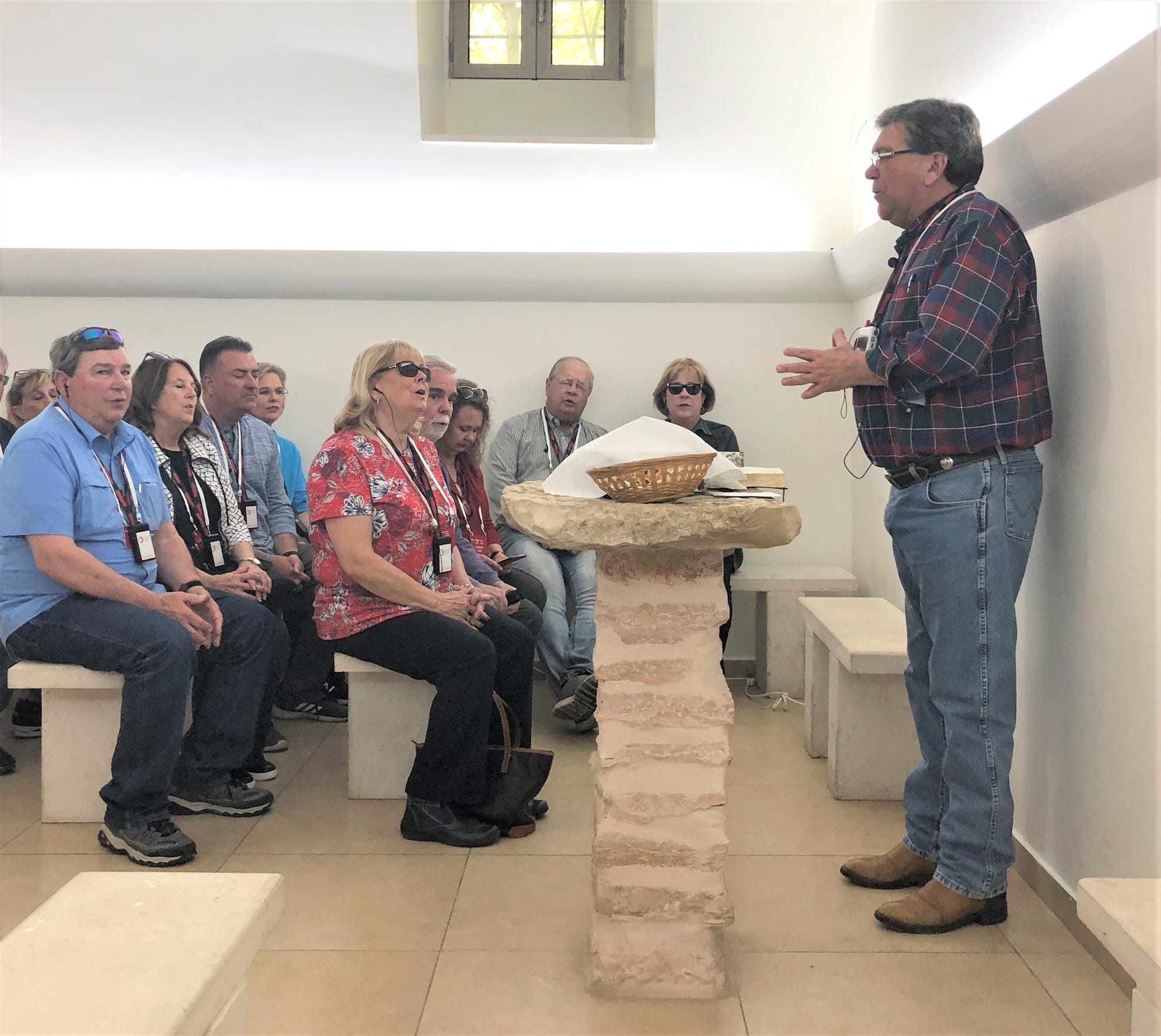 Stan Allcorn takes on a pastor's role, preparing communion for an Abilene group that was in Israel this spring. They were in the chapel at the Garden Tomb.