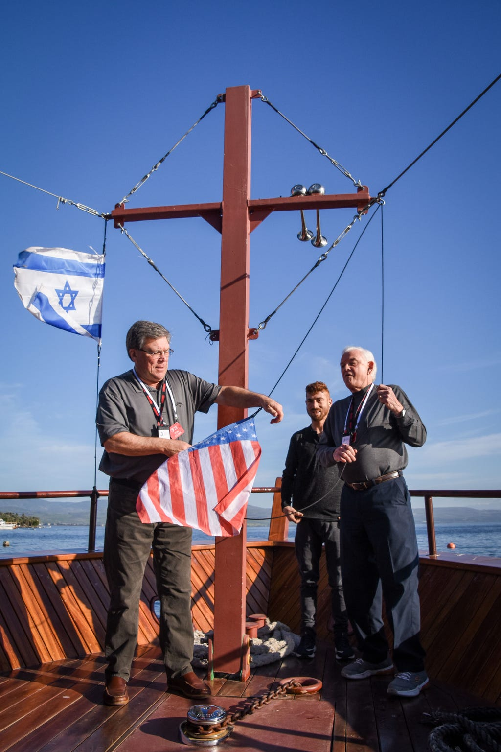 Stan Allcorn, left, and Russell Berry raise a U.S. flag on a boat on the Sea of Galilee in March.