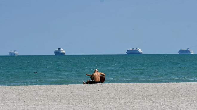 John Dedrick of Cape Canaveral plays his guitar on the beach as four cruise ships sit offshore Cocoa Beach in this age of social distancing during the coronavirus pandemic. The cruise ships take turns with other ships docking at the port. To see more photos on how Brevard is social distancing, go to floridatoday.com or click on: https://bit.ly/2VgKC4R