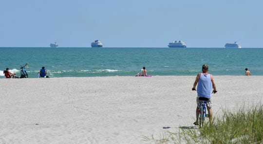 Residents of Cape Canaveral enjoy the beach as four cruise ships sit offshore earlier this month.