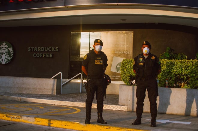 Two officials in Peru guard a supermarket in Lima during the COVID-19 coronavirus outbreak in March 2020.
