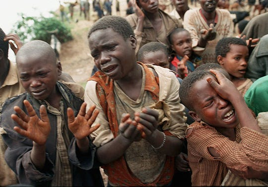 Rwandan refugee children plead with Zairean soldiers to allow them across a bridge separating Rwanda and Zaire where their mothers had crossed moments earlier before the soldiers closed the border, in this Aug. 20, 1994 file photo.