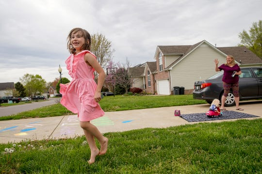 Abby Grayson, 7, left, leaps up in excitement at the sight of cars approaching covered in birthday decorations and wishes for her on her birthday at the Grayson household in Clarksville, Tenn., on Friday, April 3, 2020.