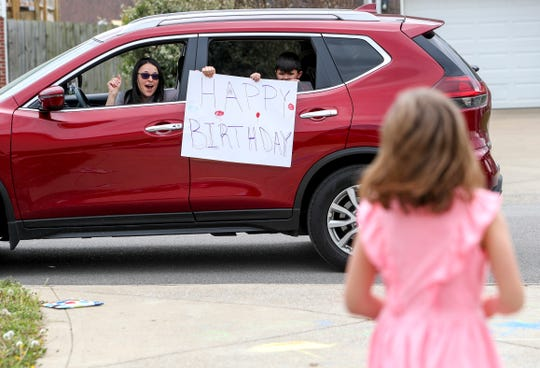 Friends and classmates park briefly at the top of the Grayson driveway to sing happy birthday for Abby Grayson, 7, right, at the Grayson household in Clarksville, Tenn., on Friday, April 3, 2020.