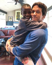 Free Press columnist Mitch Albom with Knox, 8, an orphan from the Have Faith Haiti mission.