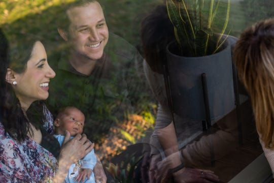 State Rep. Robert Wittenberg of Huntington Woods and his wife Kimberly and their children Ada and newborn Abel talk with Robert's mother Mollie Wittenberg of Huntington Woods in their front window on Friday, April 3, 2020. Wittenberg hasn't been able to hold her grandchild yet due to concerns with the Coronavirus.