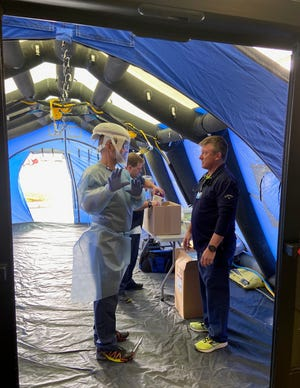 Emergency Department Manager Tom Eller, left, speaks to registered nurse Craig Warren about the screening process for patients in a  triage tent in front of McLaren Bay Region hospital in Bay City. All people attempting to enter the emergency room are initially screened prior to coming into the facility to ensure that they are accessing the correct level of care.