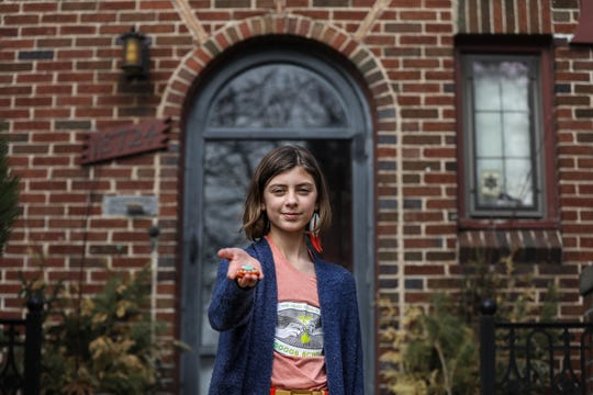 Evelyn Wybenga, 10, of Detroit holds up one fo the rocks she painted and leaves for others while out for walks with her family in the North Rosedale park neighborhood, photographed on Friday, March 27, 2020.