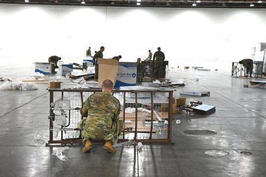 Members of the Michigan National Guard built bed frames for a  temporary hospital for patients with coronavirus at the TCF Center in Detroit on Saturday, April 4, 2020. 