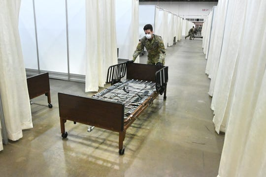 A Michigan National Guardsman prepares a cubicle for patients in a field hospital at TCF Center In Detroit.
