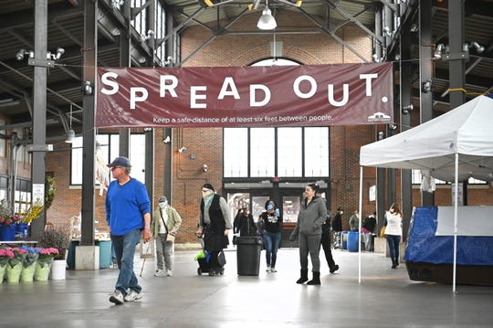 A banner reads Spread Out as shoppers continue buying produce inside Shed 3 at Eastern Market in Detroit on Saturday, April 4, 2020.