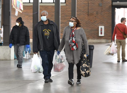 Customers wear protective masks and gloves as they carry their produce items inside shed 3 at Eastern Market in Detroit on Saturday, April 4, 2020.