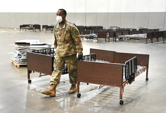 A member of the Michigan National Guard moves bed frames from Hall B to Hall C where a temporary hospital is to accommodate patients with coronavirus at the TCF Center.