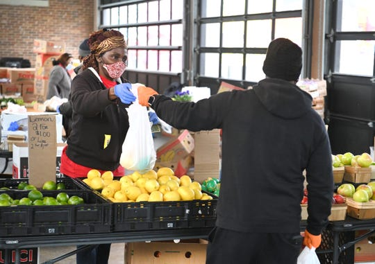 Tina Jenkins, left,  of Greg and Bo's Produce, wears her protective mask and gloves as she assists a customer inside Shed 3 at Eastern Market in Detroit on Saturday, April 4, 2020.