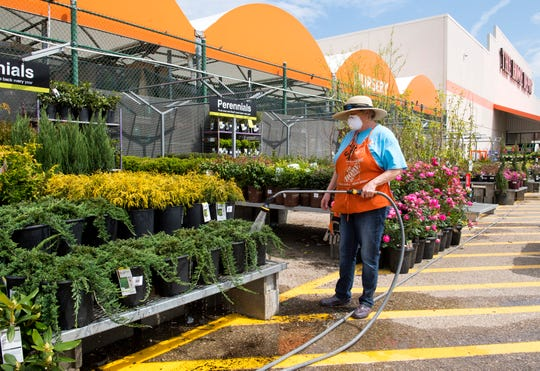 Garden associate at The Home Depot Sarah Johnson waters plants with a mask on to protect herself from the spread of COVID-19 Saturday afternoon, April 4, 2020.
