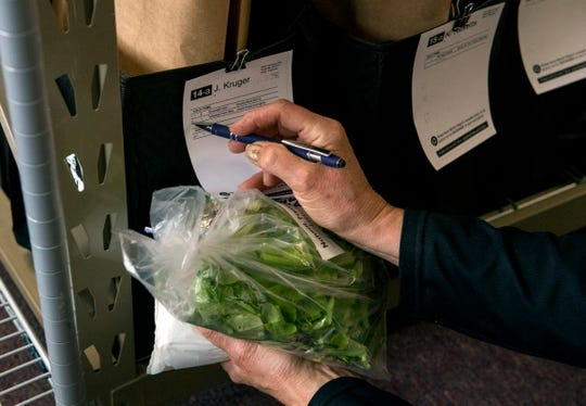 Susan Tenbarge of Tenbarge Farm Stand in Haubstadt, Ind.,  checks off lettuce as she fills a customer order for Market Wagon on delivery day Thursday morning, April 2, 2020.