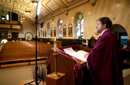 The Rev. Brian Wideman gives his homily to an empty St. Paul Catholic Church while recording himself with a phone on March 21, 2020, in Wrightstown, Wis. Wideman began recording masses for St. Clare Parish after church services were suspended to the public because of the coronavirus pandemic.