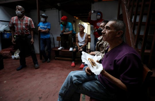 """An elderly man eats a hamburger that was donated by Emiliano Moscoso in a boarding house in Bogota, Colombia, Monday, March 30, 2020. Moscoso recently launched a program called """"Solidarity Menu"""" to feed people in need during the coronavirus outbreak . (AP Photo/Fernando Vergara)"""