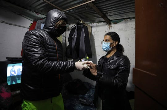 Emiliano Moscoso, left, gives a hamburger to a man from Venezuela in a boarding house in Bogota, Colombia, Monday, March 30, 2020. Moscoso recently launched a program called Solidarity Menu to feed people in need during the coronavirus outbreak. (AP Photo/Fernando Vergara)