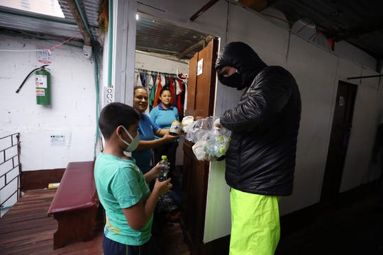Emiliano Moscoso, right, gives a hamburger to a Venezuelan family in a boarding house in Bogota, Colombia, Monday, March 30, 2020. Moscoso recently launched a program called Solidarity Menu to feed people in need during the coronavirus outbreak. (AP Photo/Fernando Vergara)