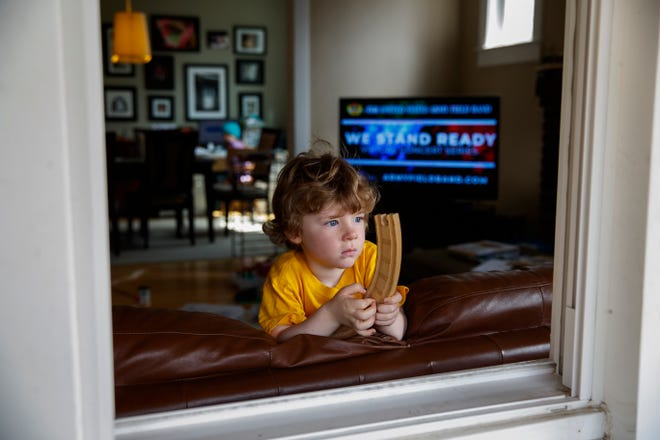 "Ethan McIver, 4, son of U.S. Army Field Band member Sgt. Major Robert McIver, Jr., holds part of his toy train set as he looks out the window of his home in Catonsville, Md., Thursday, March 26, 2020. The family is staying home because of the coronavirus outbreak. Inside on the television the U.S. Army Field Band's daily ""We Stand Ready"" virtual concert series from Fort George G. Meade is playing. The Army Field Band's mission is to bring the military's story to the American people. And they're not letting the coronavirus get in the way. (AP Photo/Carolyn Kaster)"