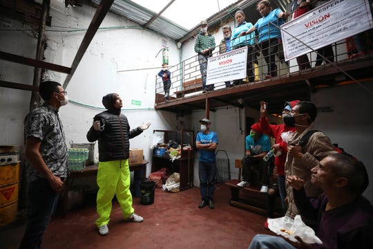 Emiliano Moscoso, second from left, talks to Venezuelan and Colombian people in a boarding house in Bogota, Colombia, Monday, March 30, 2020. Moscoso recently launched a program called Solidarity Menu to feed people in need during the coronavirus outbreak. (AP Photo/Fernando Vergara)
