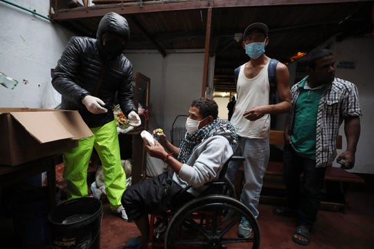 Emiliano Moscoso, left, gives a hamburger to a disabled man in a boarding house where Venezuelan and Colombian citizens live in Bogota, Colombia, Monday, March 30, 2020. Moscoso recently launched a program called Solidarity Menu to feed people in need during the coronavirus outbreak. (AP Photo/Fernando Vergara)