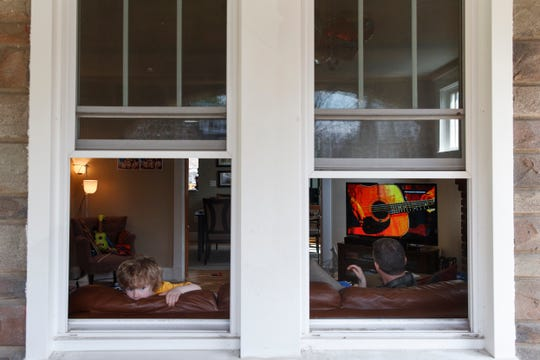 "Ethan McIver, 4, son of U.S. Army Field Band member Sgt. Major Robert McIver, Jr., right, looks out the window of their Catonsville, Md., home, Thursday, March 26, 2020. The family is staying home because of the coronavirus outbreak. Inside on the television the U.S. Army Field Band's daily ""We Stand Ready"" virtual concert series from Fort George G. Meade is playing. The Army Field Band's mission is to bring the military's story to the American people. And they're not letting the coronavirus get in the way. (AP Photo/Carolyn Kaster)"