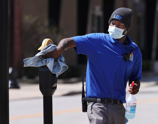 Noah Powell, of Block by Block cleaning service, used disinfectant to clean parking meters along Washington Street in downtown Louisville, Ky. on April 4, 2020.  They are trying to keep the meters sanitized as the coronavirus pandemic continues to spread.