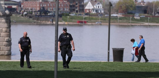 Louisville Metro Police officers patrolled Waterfront Park on Saturday. People appeared to be observing the mayor's request to not gather in large groups in the city's parks.