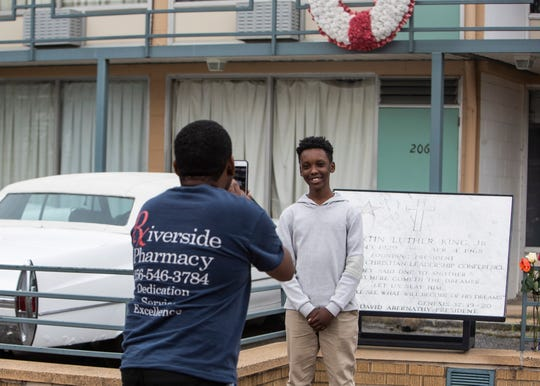 Nelson Mwangi takes a photograph of his son Ryan Mwangi in front of the National Civil Rights Museum, formerly the Lorraine Motel, on the 52nd anniversary of the assassination of Rev. Martin Luther King Jr., Saturday, April 4, 2020, in Memphis, Tenn.