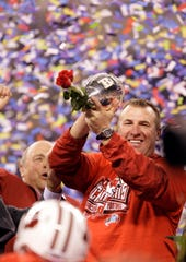Wisconsin coach Bret Bielema holds the trophy after winning the Big Ten title in 2011.