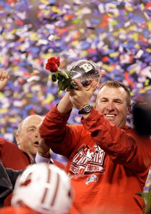 Wisconsin Badger head coach Bret Bielema holds the Big Ten title trophy after winning the Big Ten title in 2011.