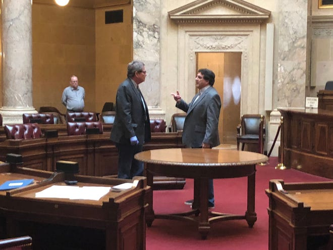 State Sen. Tim Carpenter, left, talks to Senate Clerk Jeff Renk just before the 5-second-long special session on delaying the election Saturday, April 4, 2020, at the state Capitol in Madison, Wis. The Senate — with just two of 33 members present — took no action but left open the option of returning Monday.