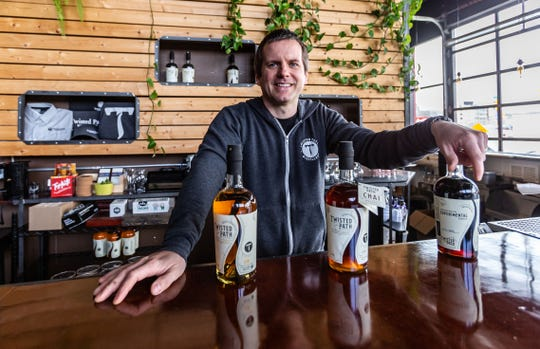 Owner Brian Sammons of Twisted Path Distillery is pictured with several of his innovative, certified organic and gluten free spirits. Sammons, a self-taught small-batch distiller, has been mixing up batches of hand sanitizer at his Bay View establishment for donation to area homeless shelters, food pantries and non-profits.