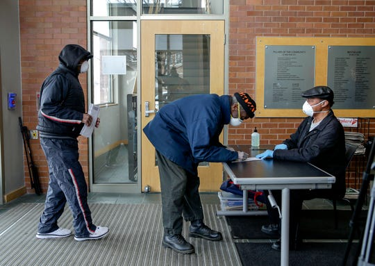 Voters with face masks come to drop off their ballots on Saturday, April 4, 2020, at the Washington Park Library.