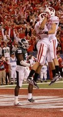Jeff Duckworth (in air, left) celebrates his first quarter touchdown with teammate Jared Abbrederis in the 2011 Big Ten title game.
