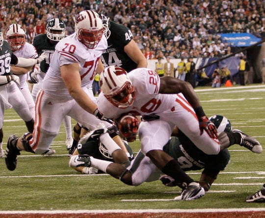 Badgers center Kevin Zeitler (70) pushes away defenders as Montee Ball scores a first quarter touchdown in the Big Ten Championship game in 2011.