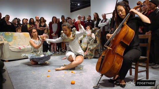 Dancers from NMSU's Kinesiology department engage in an improvisational performance with a cellist.