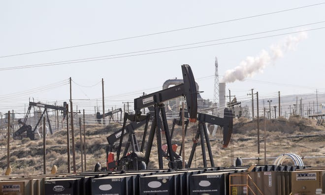 Oil derricks and other infrastructure pump oil and gases as well as dominate the landscape in Kern County, California, February 20, 2020.