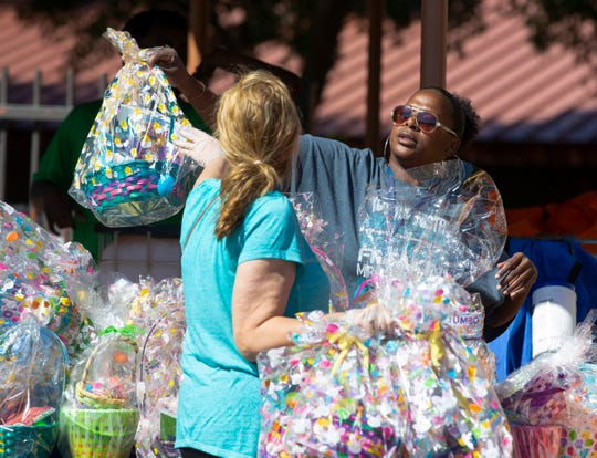 Susan Quercia, left, and Zaneta Berry help distribute Easter baskets from Phoenix Rescue Mission at Sullivan Elementary School to about 200 under-served families on April 4, 2020.
