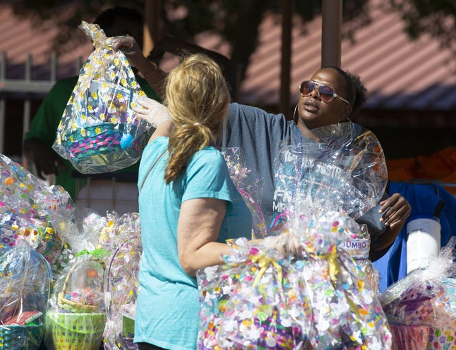 Susan Quercia, left, and Zaneta Berry help distribute Easter baskets from Phoenix Rescue Mission at Sullivan Elementary School to about 200 underserved families on April 4, 2020.
