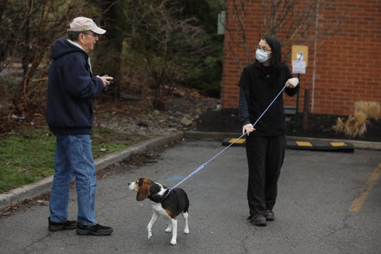 Many veterinarian hospitals, including Pittsford Animal Hospital, are closed to people going inside the hospital to prevent the spread of COVID-19, instead they call after they arrive with their pets on Saturday, April 4, 2020.  Carl Holland of Webster talks to Sarah Moshier, kennel attendant, before she takes his dog inside.  She had gone to his car to get the dog while he waited outside his vehicle in the parking lot.