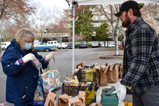 Barb Marquez takes out her wallet to purchase mushrooms from Rain Forest Mushroom Co. at the Salem Saturday Market on April 4, 2020.