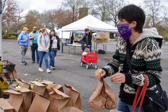 Shawn Newswanger makes her selection at the Rain Forest Mushroom Co. booth at the Salem Saturday Market on April 4, 2020.
