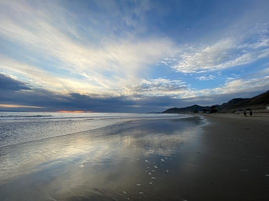 Clouds are reflected on wet sand as the sun sets near Emma Wood State Beach north of Ventura in March 2020.