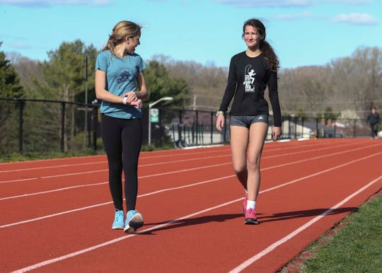 Conrad freshman Mallory Holloway (left) gets set for a workout on the McKean High School track with teammate Michaela Gates. Holloway has found success in cross country and track despite being born with cystic fibrosis.