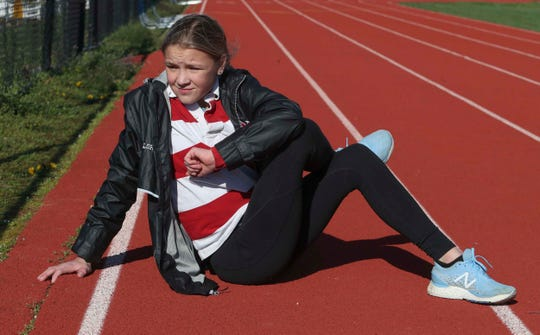 Mallory Holloway stretches after a workout on the McKean High School track. The Conrad freshman has found success in cross country and track despite being born with cystic fibrosis.