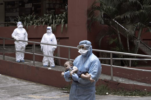 Government health workers evacuate suspected coronavirus victims from a condominium in Kuala Lumpur, Malaysia, on April 4, 2020.